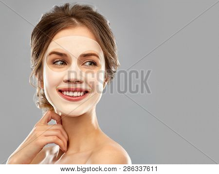 beauty, cosmetology and rejuvenation concept - smiling young woman with hydrogel or sheet facial mask over grey background