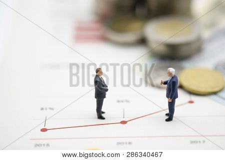Miniature Business Men Discuss On  Line Chart Of Business Growth .copy Space And Business Concept. -
