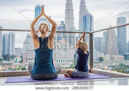 Mom And Son Are Practicing Yoga On The Balcony In The Background Of A Big City. Sports Mom With Kid
