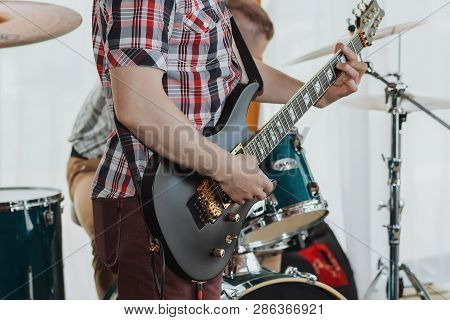 Guitarist Playing His Acoustic Guitar At A Local Concert With His Band And Another Guitarist In The