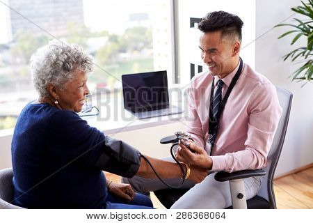 Male Doctor In Office Checking Senior Female Patients Blood Pressure