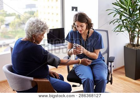 Nurse Wearing Scrubs In Office Checking Senior Female Patients Blood Pressure