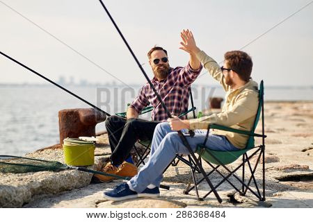 leisure and people concept - happy friends with fishing rods on pier at sea