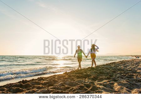 Happy Romantic Middle Aged Couple Enjoying Beautiful Sunset Walk On The Beach. Travel Vacation Retir