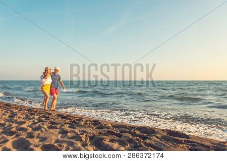 Happy Romantic Middle Aged Couple Enjoying Beautiful Sunset Walk On The Beach. Travel Vacation Retir