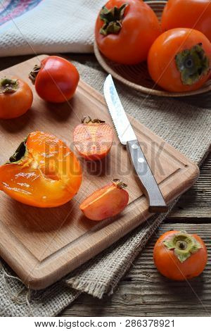 Different Varieties Of Persimmons On Wooden Background. Delicious Ripe Orange Persimmon. Organic Fru