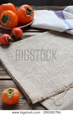 Rustic Composition With Different Varieties Of Persimmons And Wooden Cutting Board. Country Style. B