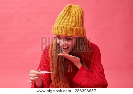 Recovering Girl Holding Pills And A Thermometer. Red Background.