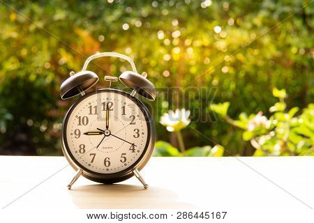 The Alarm Clock Stack On Wood Table And Sunset Background In The Public Park Show Indicates Start Or