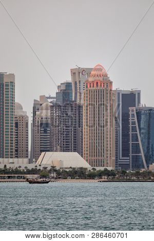 DOHA, QATAR - January 30, 2017: View across Doha Bay. to the hotels and businesses of the high rise Dafna district, lit up as night approaches