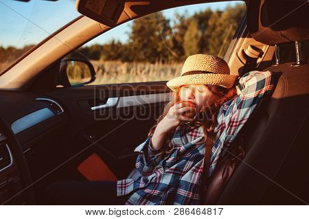 Happy Child Girl Eating Apple In Car. Summer Road Trip Concept, Lifestyle Shot