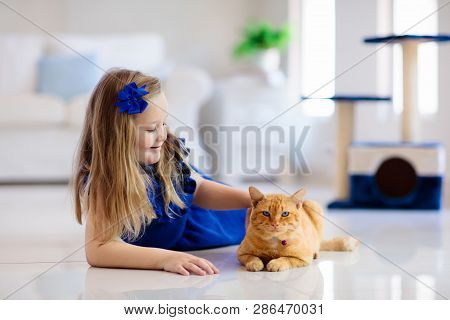 Child Playing With Cat At Home. Kids And Pets. Little Girl Feeding And Petting Cute Ginger Color Cat