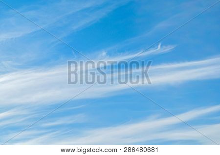 Sky background - dramatic sunset clouds lit by evening sunset light, evening sky view. Picturesque sky landscape, colorful vast sky with fluffy clouds