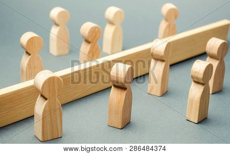 Wooden Figures Of People Are Separated By A Barrier. Social Classes. Competition Between Teams. The