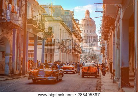 HAVANA,CUBA - FEBRUARY 23,2019 : Colorful street in Old Havana at sunset with old cars and the Capitol building