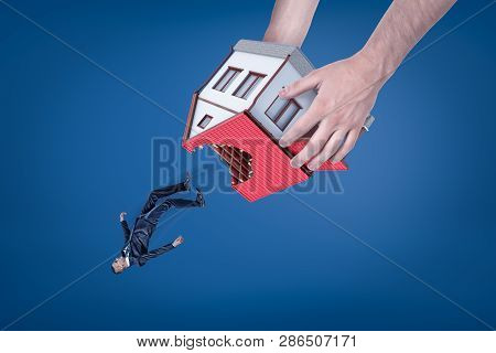 Close-up Of Mans Hands Holding House With Hole In Roof Upside Down And Dropping Out Little Businessm