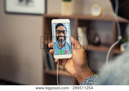 Closeup hands of african man holding smartphone doing video calling with friend. Portrait of latin man on conversation with businessman on smartphone. Man video conferencing with indian man.