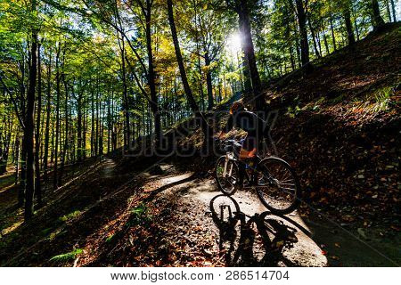 Cycling woman riding on bike in summer mountains forest landscape. Woman cycling MTB flow trail track. Outdoor sport activity.
