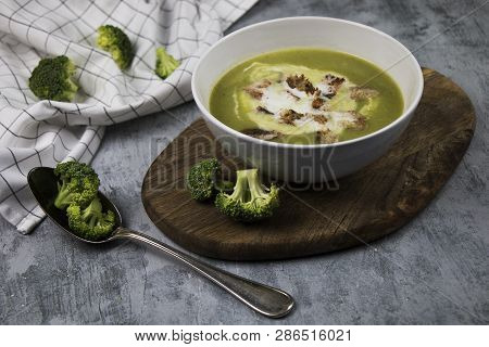 Photo Of Served Brocoli Creamy Soup With Cream And Bread Croutons On Rustic Table With Spoon And Fre