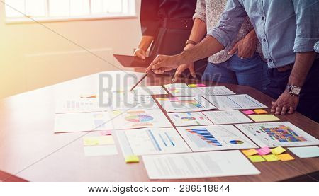 Businessman and business woman discussing on stock market charts in office. Closeup of business hands in meeting room discussing on graphs. Indian man pointing at document with colleagues around him.