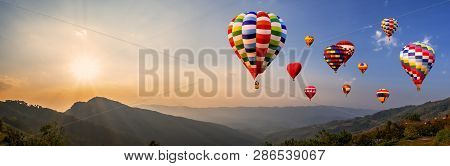 Panorama Of Colorful Hot Air Balloon Fly Over Mountain View With Sunlight,  Blue Sky And White Cloud