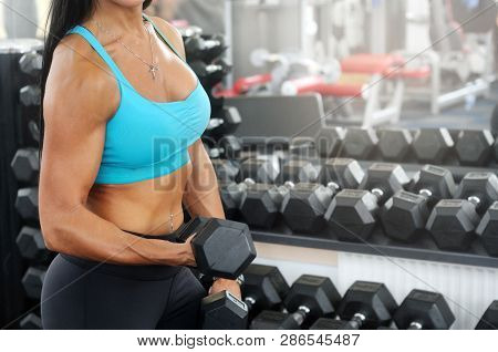Sporty Woman Workout With Dumbbell In Gym