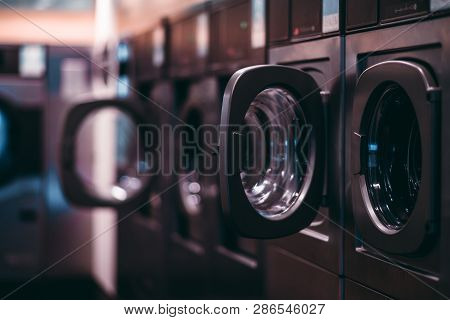 A Dark Room Of A Publiс Laundry With A Row Of Empty Washing Machines Inside, Selective Focus On The