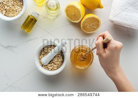 Partial View Of Female Hand With Honey Stick, Pounder With Oat Flakes, Lemons And Different Natural