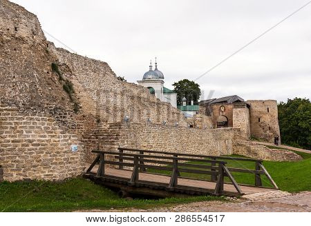 The Izborsk fortress. The ruins of the oldest stone fortress in Russia. The walls of the fortress and orthodox church of St. Nicholas in the Izborsk fortress. Izborsk, Pskov region, Russia poster