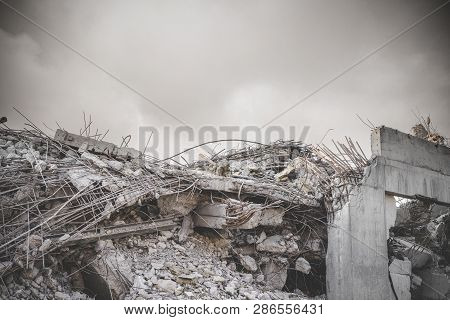 Ruin In A War Zone With A Damaged Concrete Building Under A Cloudy Sky