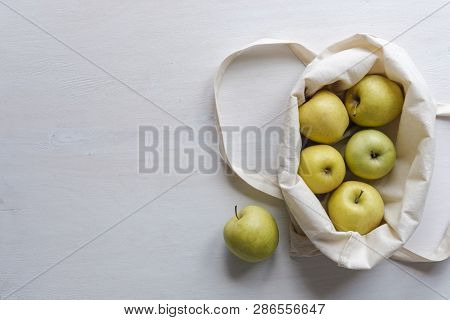 Fresh Golden Apples In A Neutral Natural Fiber Re-usable Cloth Shopping Bag Viewed From Above With C