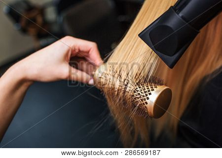 Close-up Of Hairdressers Hand Drying Blond Hair With Hair Dryer And Round Brush. Doing Hairstyle In
