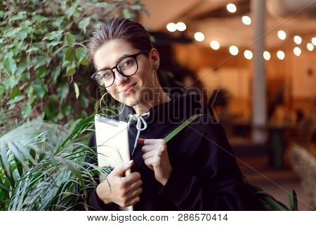 Shortcut Student Girl In Eyewear Standing With Tablet Near The Plants At The Cafe