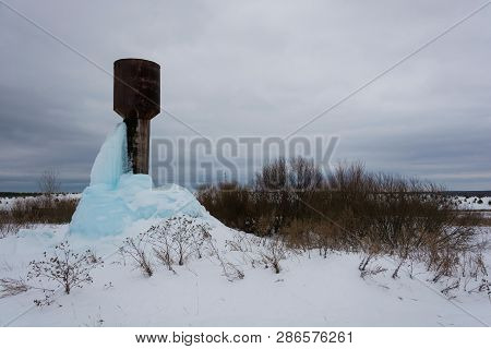 High Water Tower With A Large Block Of Blue Ice.