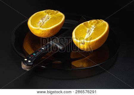Still Life With Orange Oranges And A Large Knife On A Dark Plate.