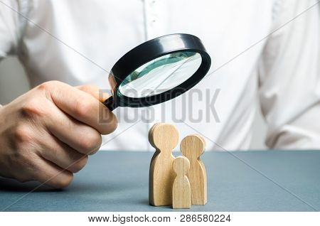 A Man Looks Through A Magnifying Glass At A Family Figure. The Study Of Family Composition And Demog