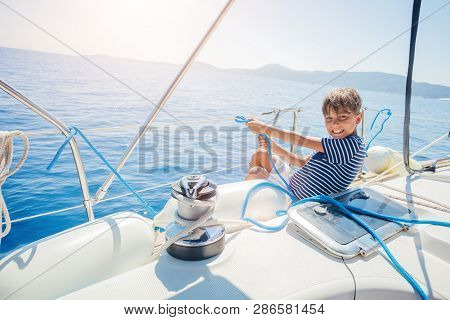 Little Boy On Board Of Sailing Yacht On Summer Cruise. Travel Adventure, Yachting With Child On Fami