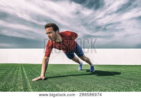 One Arm Pushup bodyweight exercise strong man working out muscles with advanced variation of push-ups. Push up training at gym.