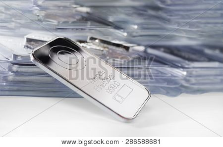Minted Silver Ingot Weighing One Troy Ounce Against The Background Of A Large Number Of Packaged Bar