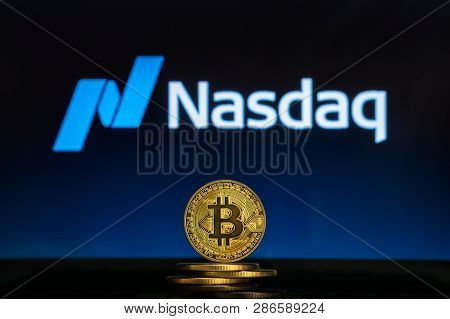 Bitcoin On A Stack Of Coins With Nasdaq Logo On A Laptop Screen. Cryptocurrency And Blockchain Adopt