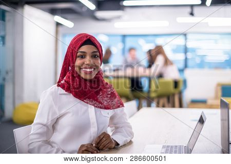 Young modern black muslim business woman wearing a red hijab,working on laptop computer in startup office. Diversity, multiracial concept