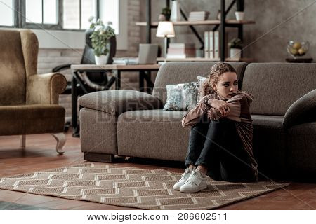 Teenage Girl Feeling Discouraged And Depressed Sitting At Home Alone