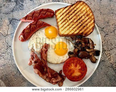 Aussie / Australian Breakfast With Brioche Toast, Fried Eggs, Crispy Bacon Sausage And Mushrooms.