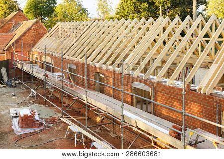 Uk Building Site With Scaffolding. Part Of A Period House Is Restored Using Modern Building Methods.