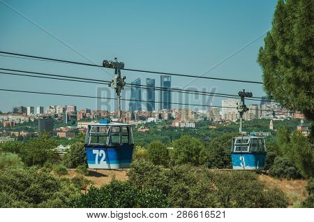 Cable Car Gondola Passing Through Leafy Trees And Buildings Skyline, In A Sunny Day At The Teleferic