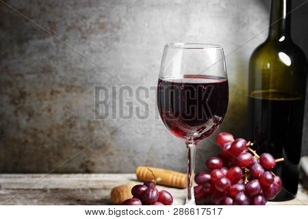 Glass Of Red Wine On A Wooden Table In A Rustic And Vintage Wine Bar With Grapes And A Bottle Of Win