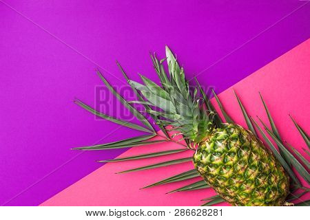 poster of Ripe pineapple on green palm leaf on duotone fuchsia pink vibrant violet background. Trendy funky style neon colors. Summer vacation tropical theme beach party.Flat lay copy space