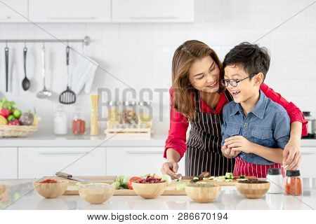 Asian Family Mom In Red Shirt And Black  Apron Is Teaching Her Son Use  Tool To Peel Fruit And Veget