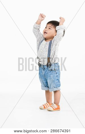 Studio Portrait Of Cute, Adorable, Asian Toddler Boy Wearing Denim Overalls, Long Sleeve T-shirt, Or