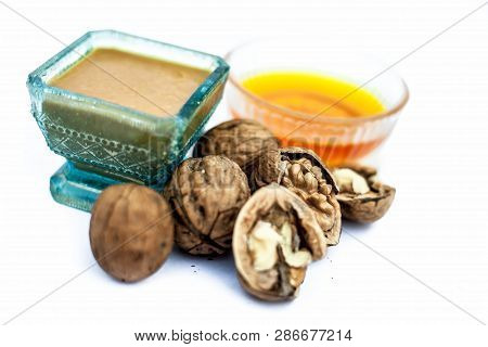 Close up of best home remedy to treat Anemia in a glass bowl isolated on white consisting of walnut powder and raw organic honey. poster